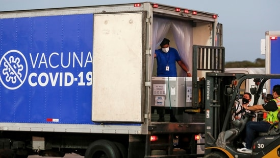 Containers of AstraZeneca vaccines under the Covax scheme are loaded onto a truck after arriving at an airport, in San Luis Talpa, El Salvador.(Reuters)