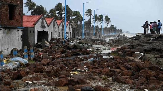 People walk through a damaged shoreline after Cyclone Yaas hit eastern coast in the Bay of Bengal, at a beach in Shankarpur, some 180 km from Kolkata on May 27. (AFP)