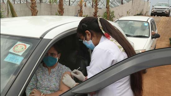 A woman takes her first dose of Covid vaccine at a drive-through vaccination centre in Mohali earlier this month. (HT file photo)