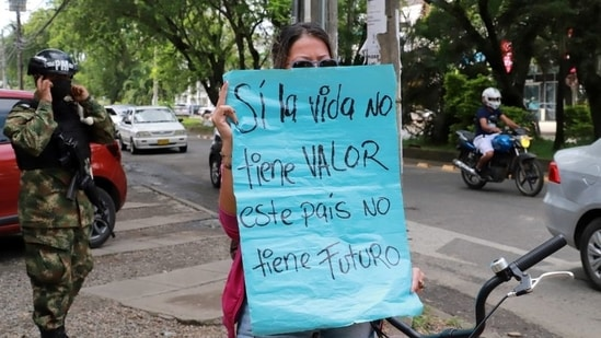 """A demonstrator holds a sign reading, """"If life has no value, this country has no future"""", next to a security force member in Cali, as Colombia will begin """"the maximum deployment"""" of military personnel in the western province of Valle del Cauca and its regional capital, President Ivan Duque said.(REUTERS)"""
