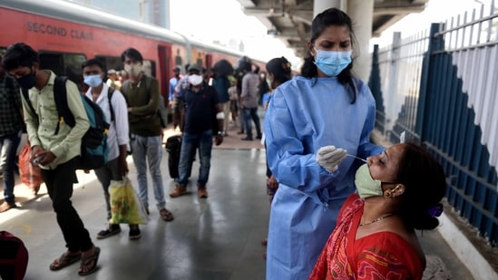 A healthcare worker wearing protective gear collects swab samples of passengers arriving from outstation trains at Dadar station in Mumbai.(HT Photo)