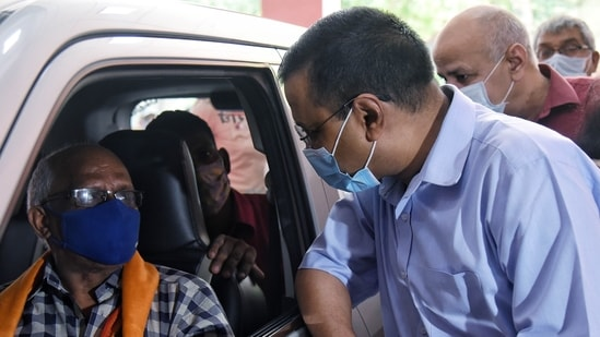 Delhi Chief Minister Arvind Kejriwal and Delhi Deputy CM Manish Sisodia interact with people during a drive-in vaccination at Chhatrasal Stadium in New Delhi.