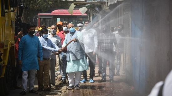 MCD mayor, Jai Prakash along with his workers seen sanitizing the streets as a preventive measure from coronavirus at Anand Parbat in New Delhi, India, on Saturday, May 29, 2021. (Photo by Sanchit Khanna/ Hindustan Times)