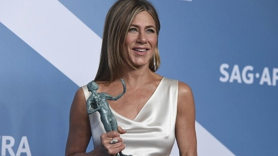 """Jennifer Aniston poses in the press room with the award for outstanding performance by a female actor in a drama series for """"The Morning Show"""" at the 26th annual Screen Actors Guild Awards.(AP)"""