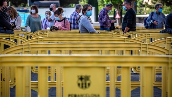 People wait in line to enter a vaccination centre in Barcelona, Spain.(Bloomberg)