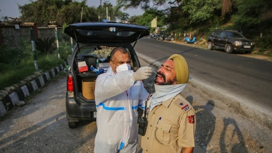 A health worker collects swab samples of a policeman for Covid-19 test in Jammu, (PTI Photo)