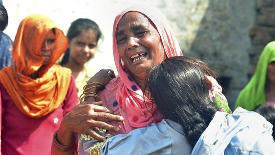 Family members mourn after more people died after allegedly consuming spurious liquor sold by a licensed vendor in Aligarh district.(PTI)