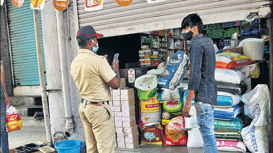 A police official takes action against a shopkeeper for operating after 11 am, near Mandai, Shukrawar peth, on Friday. (HT PHOTO)
