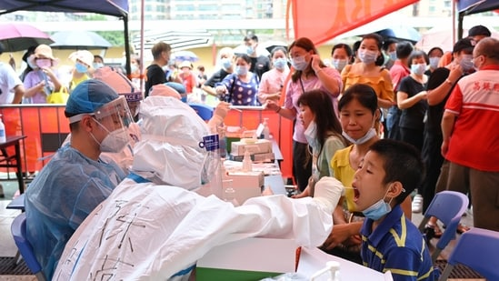 A medical worker collects a swab from a resident during a mass testing for the coronavirus disease (Covid-19) at a makeshift testing site at a stadium in Guangzhou, China.(via REUTERS)