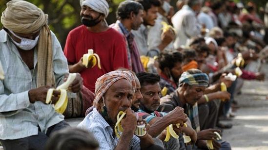 People eat food during the Langar Sewa near Kashmiri Gate, in New Delhi on Saturday. (ANI Photo)