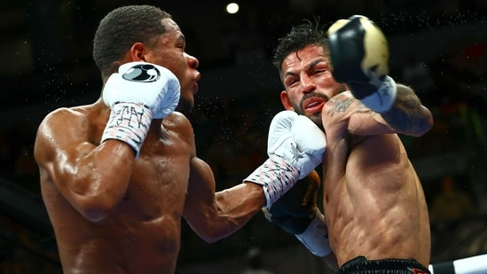 Devin Haney, left, punches Jorge Linares during the WBC lightweight title boxing match.(AP)