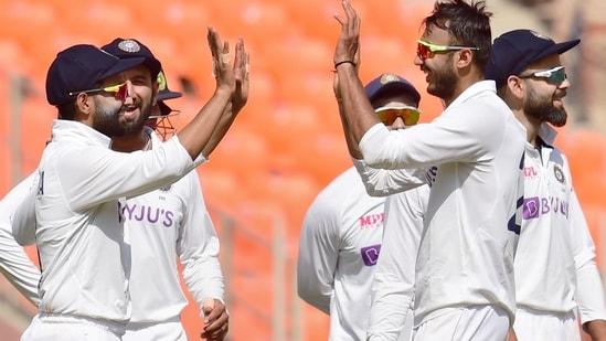Indian bowler Axar Patel (R) celebrates with teammates(PTI)