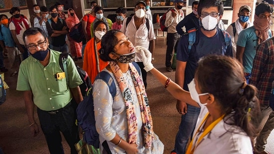 A health worker collects swab sample from a passenger for Covid-19 testing at Patna railway station.(PTI)