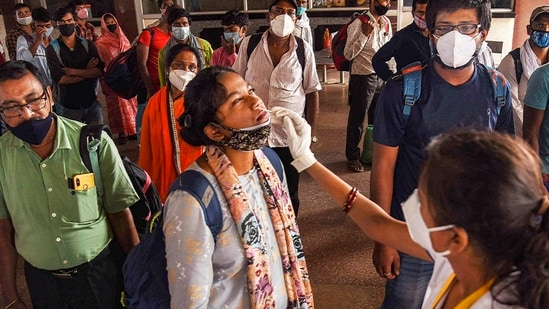 A health worker collects swab sample from a passenger for Covid-19 testing at Patna railway station.