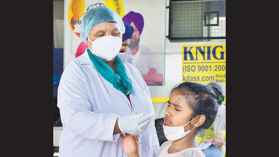 A health worker collecting swab sample of a child for Covid-19 testing near a market in Sarabha Nagar in Ludhiana on Sunday. (Harsimar Pal Singh/HT)