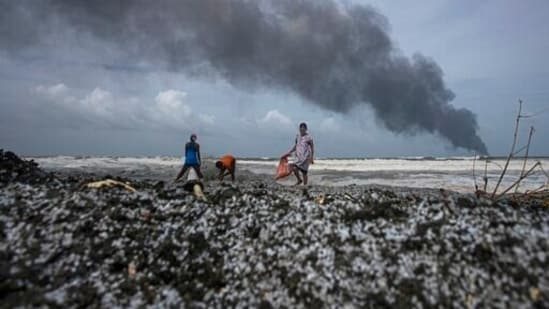 Impoverished Sri Lankans salvage wreckage washed off to the shore from the burning Singaporean ship MV X-Press Pearl which is anchored off Colombo port at Kapungoda, outskirts of Colombo, Sri Lanka.(AP)