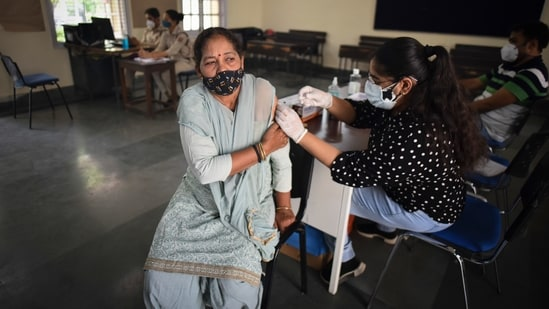 A health worker administers a Covid-19 vaccine to a beneficiary, at Mandir Marg in New Delhi.(Sanchit Khanna/HT PHOTO)