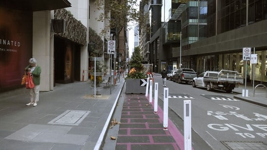 Pedestrians walk along a near deserted street during a lockdown in Australia(Bloomberg)