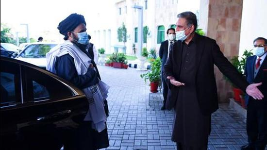Pakistan's foreign minister Shah Mehmood Qureshi gesturing to Taliban co-founder Mullah Abdul Ghani Baradar (left) upon his arrival with a delegation for talks at the Pakistan Foreign Ministry in Islamabad in December 2020. (AFP)