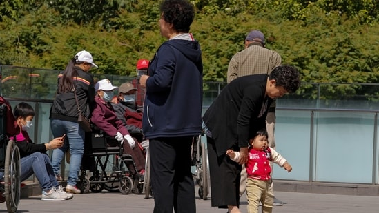The fertility rate in the world's populous nation currently stands at 1.3 which is beneath the levels needed to maintain a stable population, the latest data showed. In picture - A woman plays with a child in Beijing.(AP)