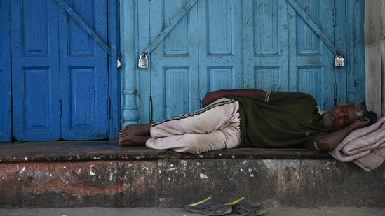 A man sleeps outside a closed shop during a lockdown imposed as preventive measure against the spread of the Covid-19 coronavirus, in the old quarters of New Delhi on May 23, 2021. (AFP)