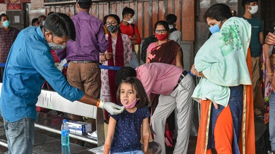 A medical worker collects swab sample of a child passenger for Covid-19 test in Lucknow. It is among the 14 districts where Covid restrictions will continue.(PTI Photo)