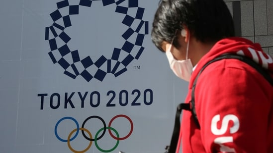 A man walks by the logo of the Tokyo Olympics, in Tokyo,(AP)