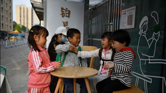 Children play outside a cafe in Beijing, China. (AFP)