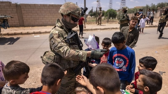 A US Army soldier hands out candy to children while on joint patrol with local allied forces on May 25, 2021 near the Turkish border in northeastern Syria.(AFP)