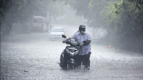 A water-logged Sutarwadi road on Monday, leaves this two-wheeler motorist with no choice but to lug his vehicle through the flooded road. (KALPESH NUKTE/HT)