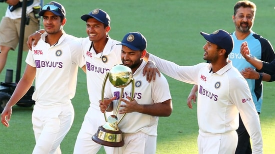 India's Rishabh Pant carries the trophy as he celebrates with his teammates after defeating Australia(AP)