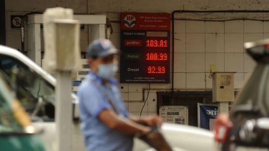 An attendant at a petrol pump, with fuel rates displayed behind him on a digital screen as petrol price reached new highs in Mumbai in this file picture from Saturday. (Vijay Bate/HT Photo)