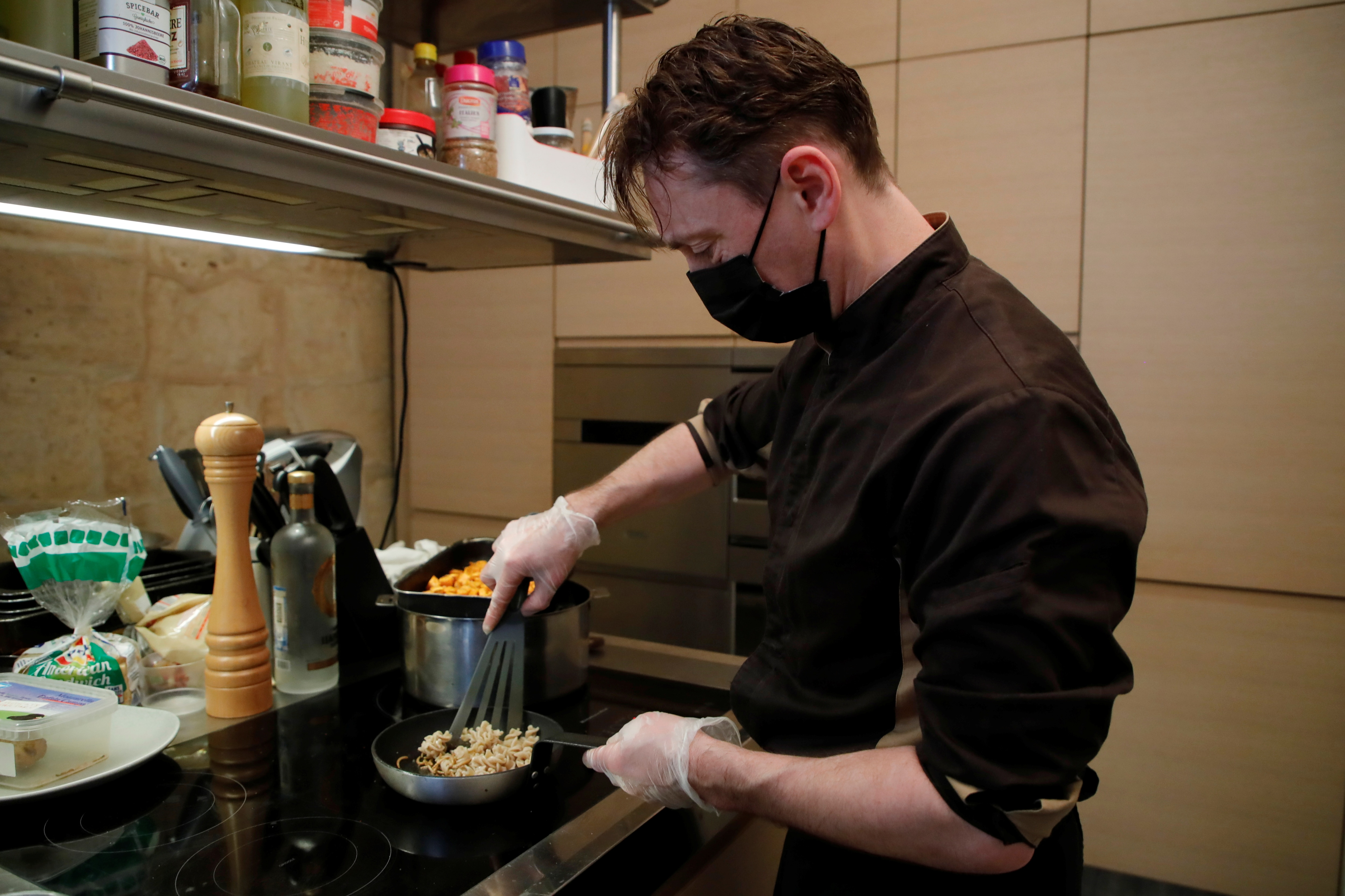 Koki Prancis Laurent Fett menyiapkan sepiring ulat goreng di restorannya, Inoveat, yang hanya menyajikan makanan berbahan serangga di Paris, Prancis (REUTERS)