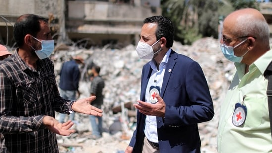 Robert Mardini, Director General of the International Committee of the Red Cross (ICRC), gestures as he speaks with a Palestinian man near the rubble of a house destroyed in Israeli airstrikes during Israeli-Palestinian fighting, in Gaza City on June 2, 2021. (Reuters)