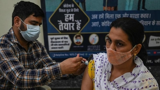 A health worker inoculates a woman with a dose of the Covishield vaccine at a civil hospital in Jind in Haryana. (AFP)
