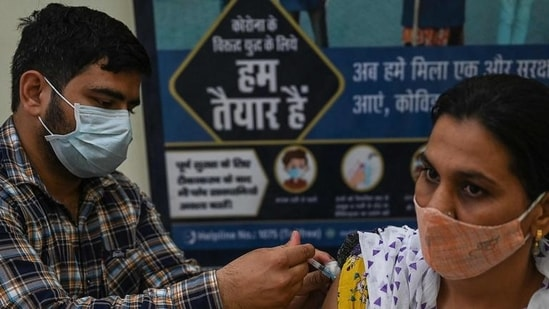 A health worker inoculates a woman with a dose of the Covishield vaccine at a civil hospital in Jind in Haryana