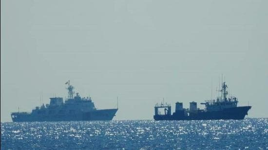A Chinese Coast Guard patrol ship (left) is seen near an unidentified vessel at South China Sea. (REUTERS)