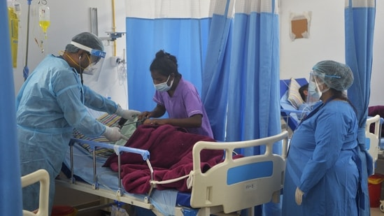 In this picture taken on June 1, 2021, a doctor (C) checks on a Covid-19 coronavirus patient at an Intensive Care Unit (ICU) of the Nightingale Hospital, on the outskirts of Siliguri.(AFP)