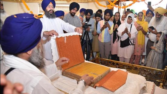 Devotees having darshan of the bullet-hit holy saroop of Guru Granth Sahib in the Golden Temple complex in Amritsar on Thursday. (Sameer Sehgal/HT)