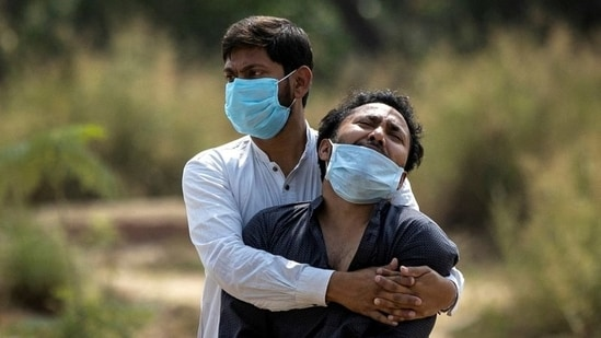 A man is consoled by his relative as he sees the body of his father, who died from complications related to the coronavirus disease in New Delhi. (Reuters file photo)