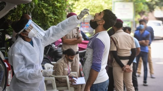 A health worker collects a swab sample for the Covid-19 test, at Kirti Nagar Industrial Area, in New Delhi, India, on Friday, June 4, 2021. (Photo by Sanchit Khanna/ Hindustan Times)