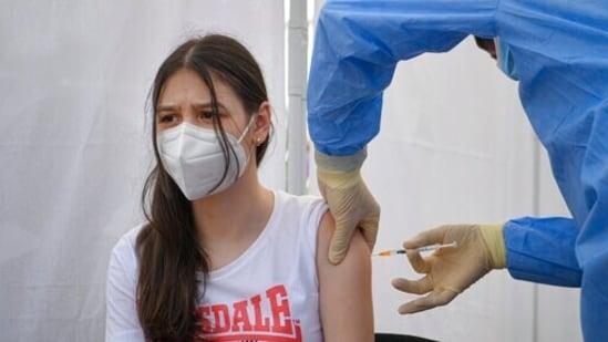 A girl gets a Pfizer BioNTech Covid-19 vaccine in Bucharest, Romania.(AP)