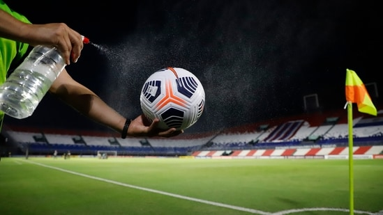 """A Conmebol worker disinfects a game ball at """"Defensores del Chaco"""" Stadium.(AP)"""