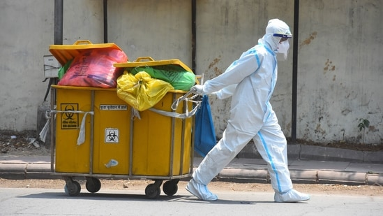 A paramedical staff wearing PPE coveralls seen disposing biomedical waste at LNJP hospital in New Delhi.(Hindustan Times)