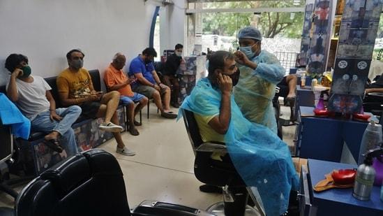 People having a haircut in a salon on Ghodbunder in Maharashtra. (Praful Gangurde / HT Photo)