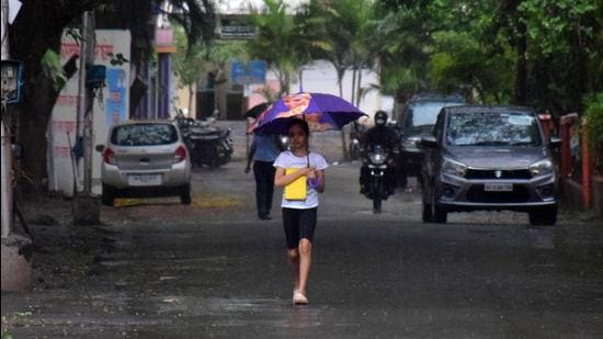 Pune, India - June 4, 2021: A girl walking in rain with umbrella on Nimhan Mala road of Pashan in Pune, India, on Friday, June 4, 2021. () (HT PHOTO)