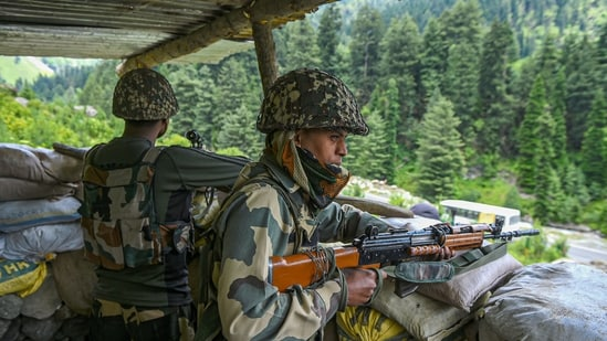 Border Security Force (BSF) personnel stand guard along the Srinagar-Leh National highway, in Ganderbal district of Central Kashmir. (PTI Photo)