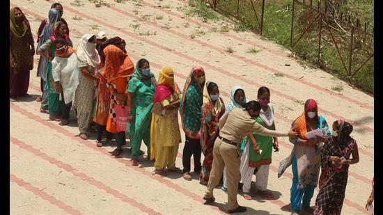 A police woman urging people to maintain social distancing during ration distribution under PM Garib Kalyan Ann Yojana at the Khuda Lohra government school in Chandigarh. (Keshav Singh/HT)