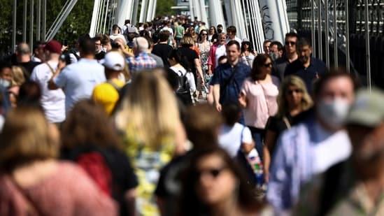 People walk across the Golden Jubilee Bridge during sunny weather, amid the coronavirus disease (Covid-19) outbreak, in London, Britain, June 5, 2021. (Reuters)