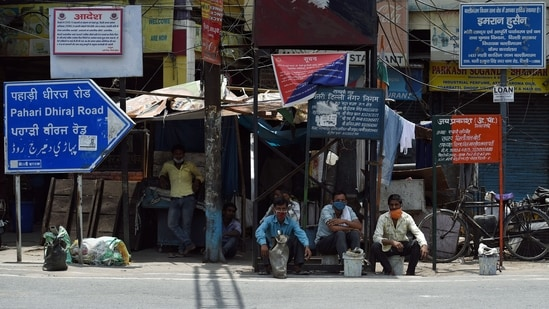 People sitting outside closed shops of Sadar Bazar during the lockdown imposed amid the rise in Covid-19 cases in New Delhi on Sunday. (ANI Photo)